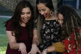 Jessica Brady, Alexis Gonzalez and Dara Salazar admire their rings after the UTSA ring ceremony May 9. How many UTSA students are aware they're eligible for a tuition rebate if they graduate in four years?