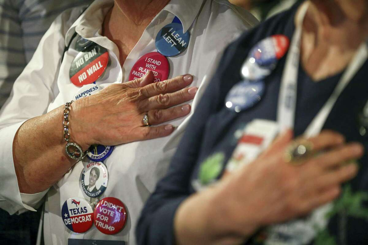 Attendees to the 2018 Texas Democratic Convention stand for the pledge of allegiance at the start of the general session at the Texas Democratic Convention Friday, June 22, 2018, in Fort Worth, Texas. (AP Photo/Richard W. Rodriguez)