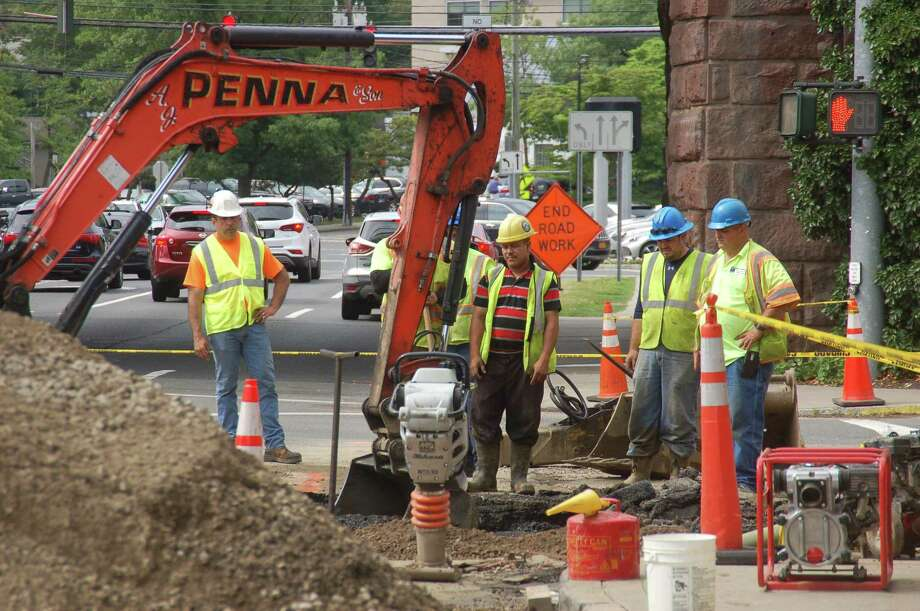 Crews from Aquarion work to repair a water main break on Friday on Arch Street near the train station in central Greenwich. Photo: Ken Borsuk /