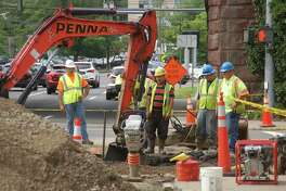 Crews from Aquarion work to repair a water main break on Friday on Arch Street near the train station in central Greenwich.