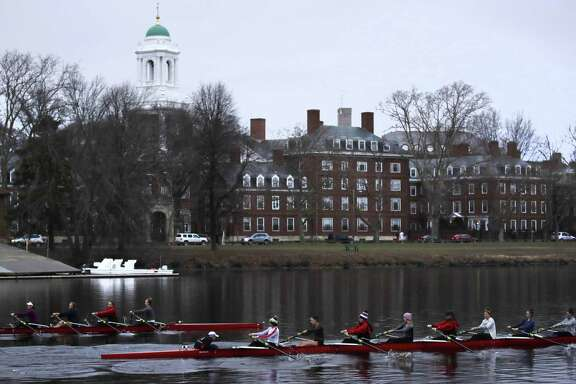 Rowers pass the campus of Harvard University in 2017 as they paddle down the Charles River in Cambridge, Mass. Harvard is the target of a lawsuit alleging discrimination against Asian-American applicants.