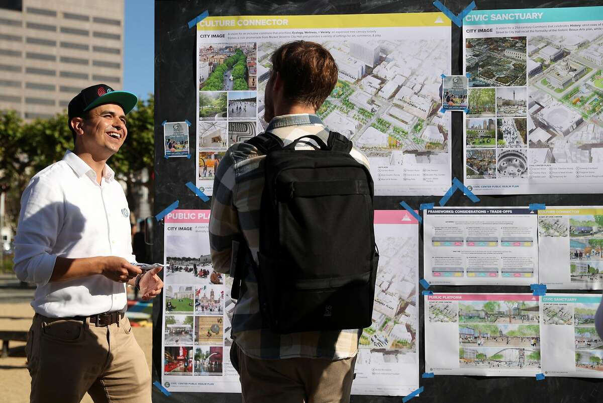 San Francisco Planning Department urban designer Nick Perry (left) shows potential plans for Civic Center Plaza during block party in San Francisco, Calif. on Thursday, June 21, 2018.