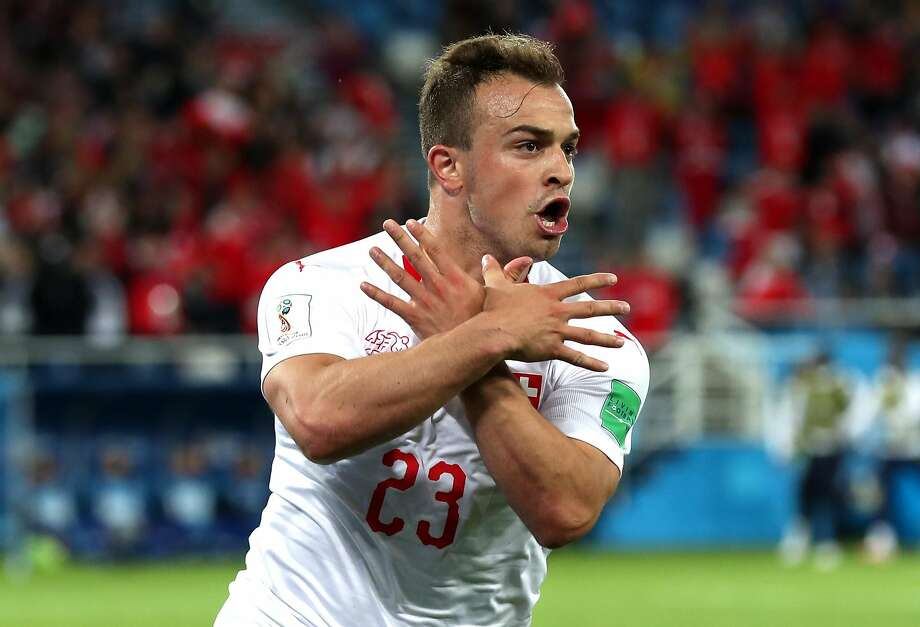 Xherdan Shaqiri of Switzerland celebrates with a hand gesture that references the Albanian national flag after scoring against Serbia. Shaqiri was born in Kosovo. Photo: Clive Rose / Getty Images