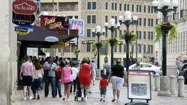 People walk on the Alamo Street sidewalk past Alamo Plaza tourist attractions.