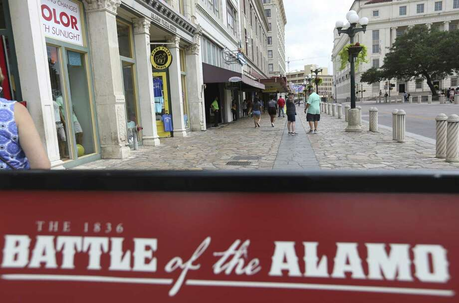 A sign explaining a part of the history of the battle of the Alamo sits June 21 on the Alamo Street sidewalk in Alamo Plaza. A design plan for the plaza is generating heat. Photo: William Luther /San Antonio Express-News / © 2018 San Antonio Express-News