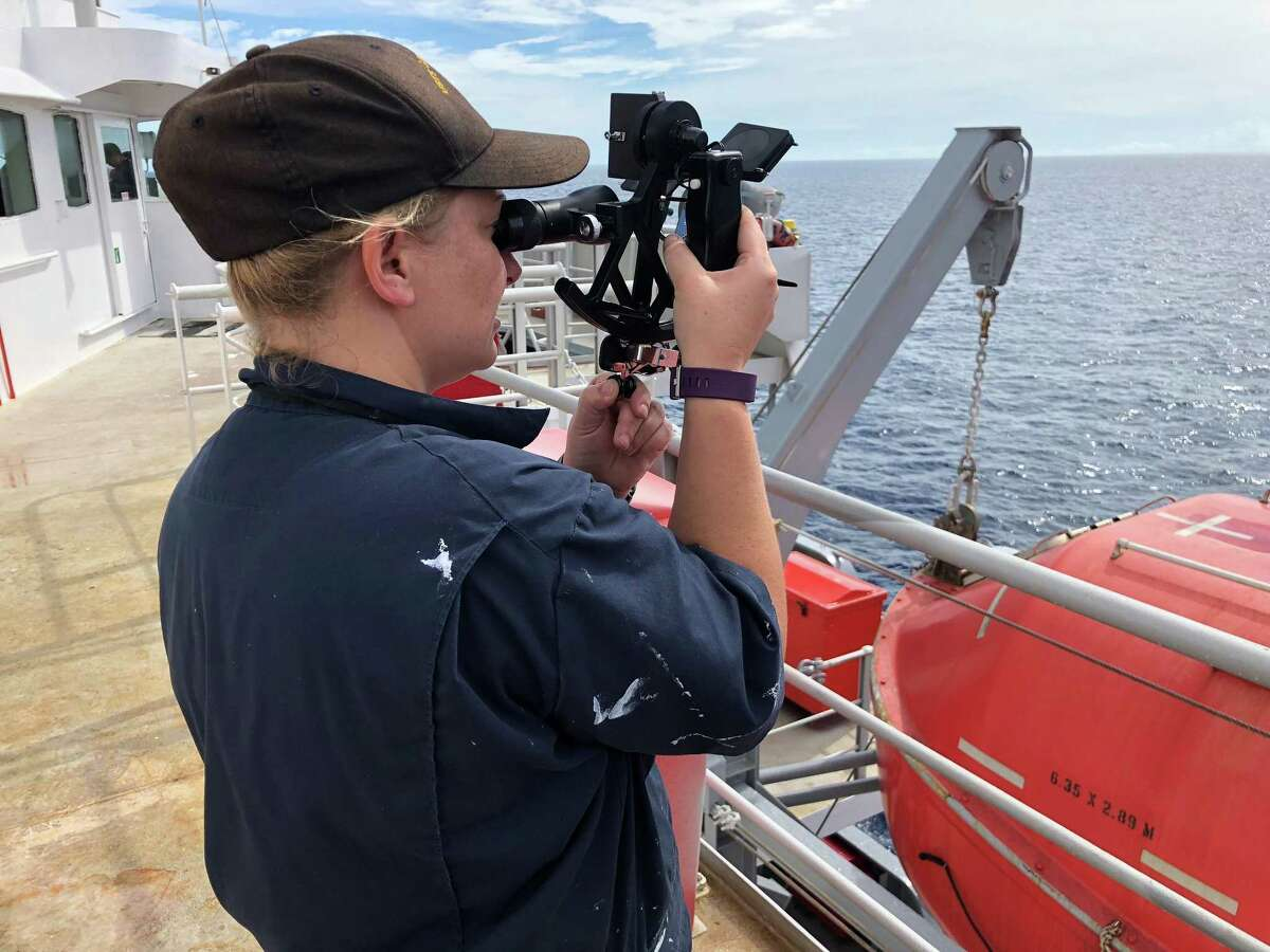 A Texas A&M Maritime Academy cadet uses a sextant for celestial navigation.