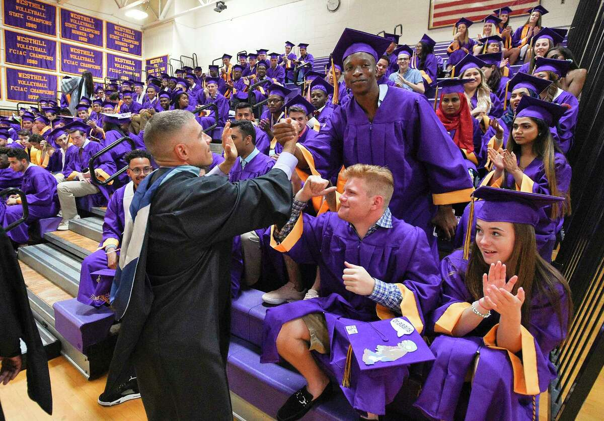 Principal Michael Rinaldi shakes hands with Melvin Andre as he walks around to get the students psych about graduation prior to Westhill High School Class of 2018 commencement exercises on June 22, 2018 in Stamford, Connecticut.
