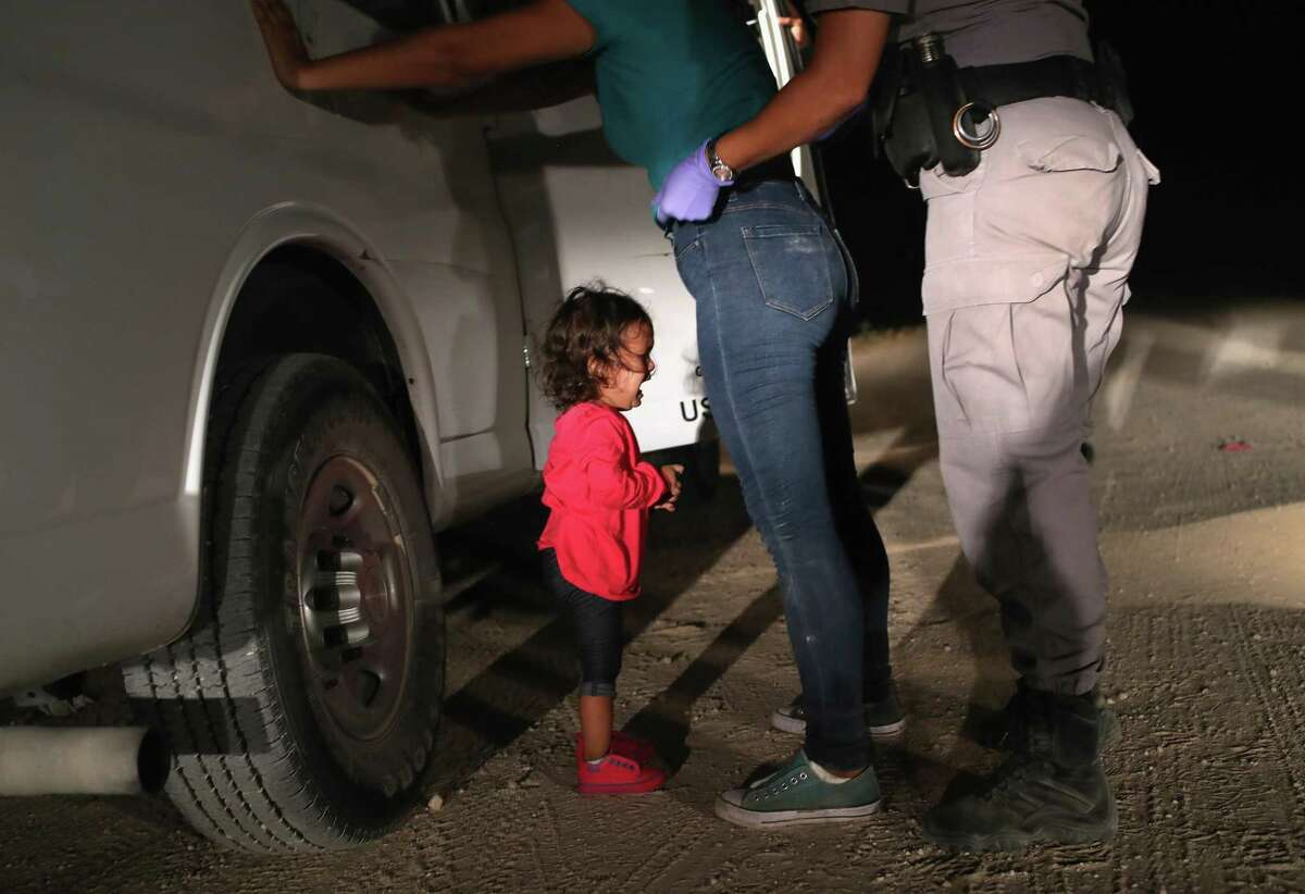 A two-year-old Honduran asylum seeker cries as her mother is searched and detained near McAllen.