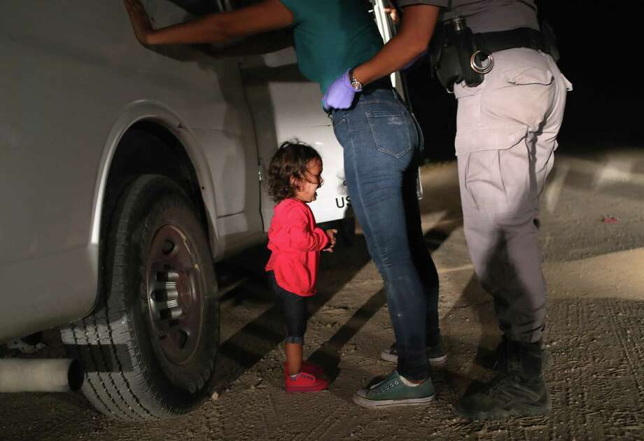 A two-year-old Honduran asylum seeker cries as her mother is searched and detained near McAllen. Photo: John Moore, Staff / Getty Images / 2018 Getty Images