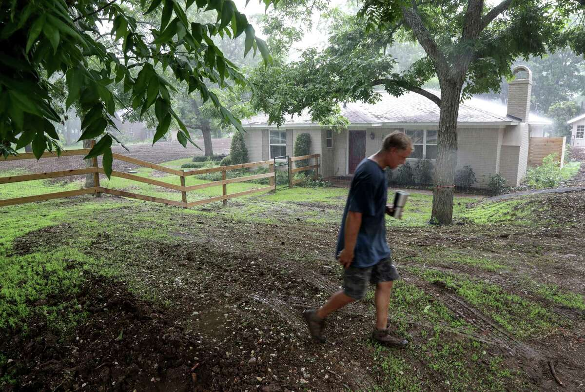Davis Bush walks along the top of a levee he had built around his home after repairing damage from Hurricane Harvey, Tuesday, June 19, 2018, in Richmond. ( Jon Shapley / Houston Chronicle )