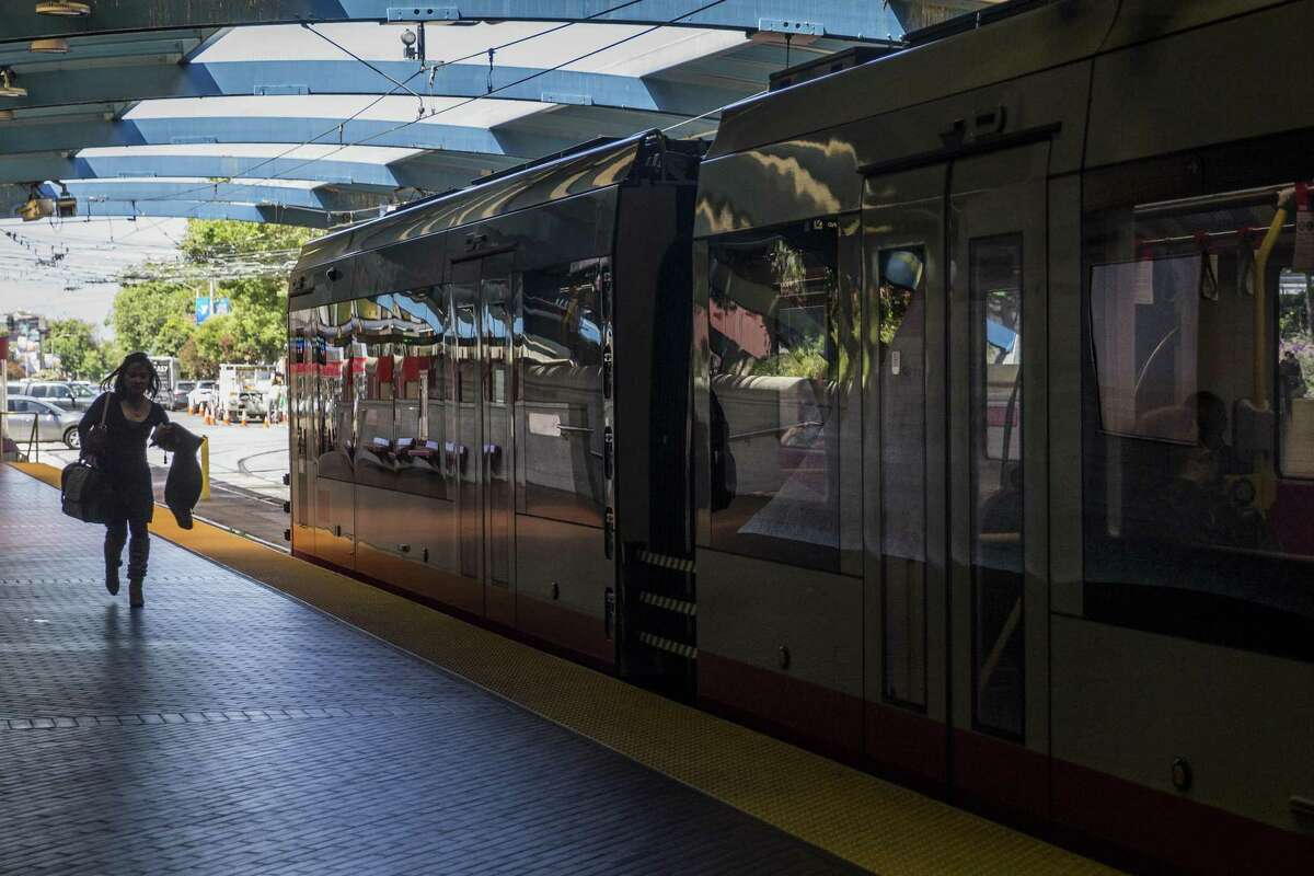 A woman runs for an inbound train at West Portal Station.