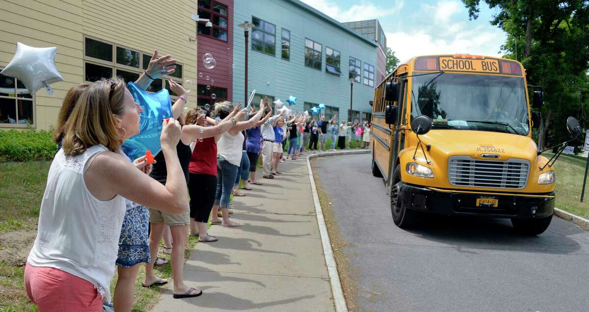 Teachers and staff at Montessori Magnet School wave to their students as their buses leave the school on the last day of school Friday June 22, 2018 in Albany, NY. (John Carl D'Annibale/Times Union)