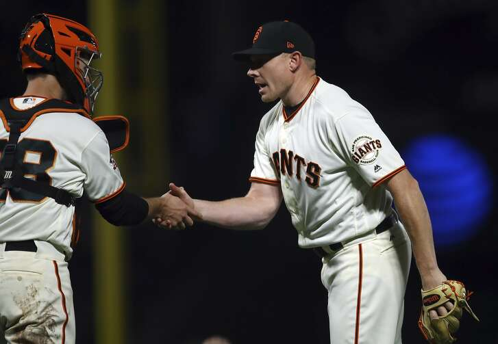 San Francisco Giants pitcher Mark Melancon, right, and catcher Buster Posey celebrate the team's 3-0 win over the San Diego Padres in a baseball game Thursday, June 21, 2018, in San Francisco. (AP Photo/Ben Margot)