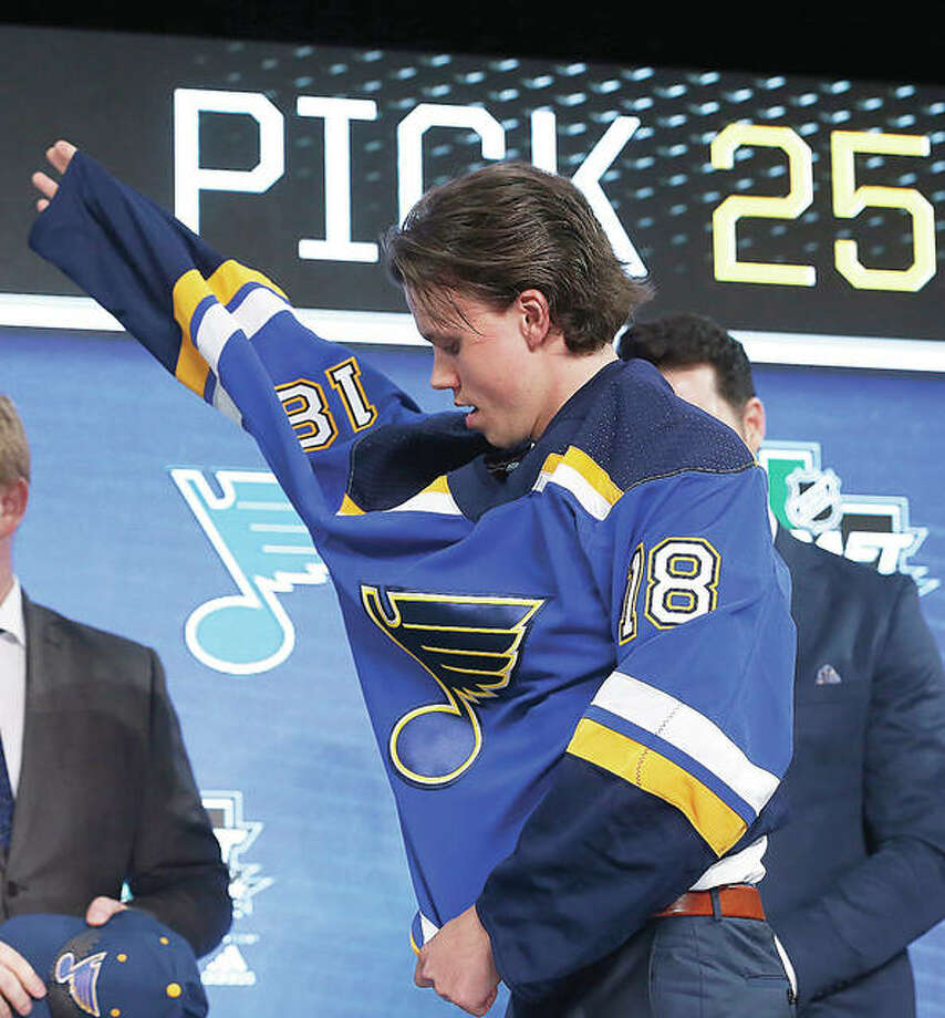 Dominik Bokk puts on a St. Louis Blues sweater after being selected in the first round of the NHL Draft Friday night in Dallas. Photo:       AP