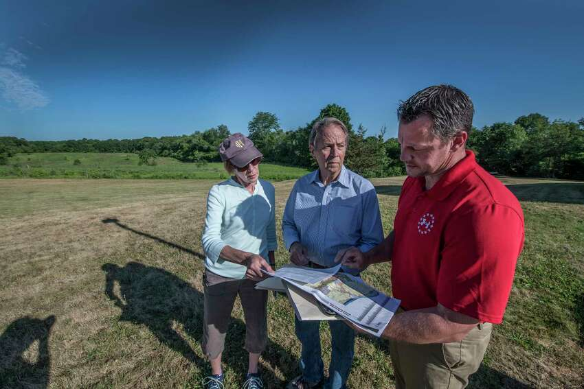 Birchwood Homeowner Association members Lynn MacGowan, left Bob Lansing, center and Adam Brunner, stand by a large field that is the proposed site of an Amazon distribution center Thursday June 21, 2018 in Schodack, N.Y. (Skip Dickstein/Times Union)