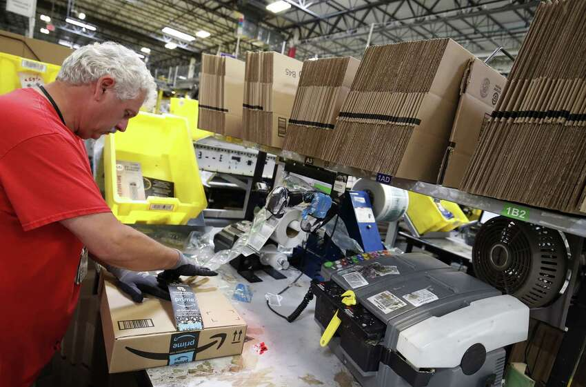 A worker prepares a package for shipment at the Amazon.com fulfillment center in Kenosha, Wisconsin, U.S., on Tuesday, Aug. 1, 2017. Amazon.com Inc. held a giant job fair at nearly a dozen U.S. warehouses as part of its effort to hire 100,000 people in the U.S. by 2018. Photographer: Jim Young/Bloomberg ORG XMIT: 775019410