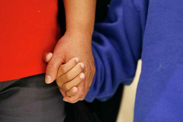 Darwin Micheal Mejia, right, holds hands with his mother, Beata Mariana de Jesus Mejia-Mejia, during a news conference after their reunion at Baltimore-Washington International Thurgood Marshall Airport, Friday, June 22, 2018, in Linthicum, Md. The Justice Department agreed to release Mejia-Mejia's son after she sued the U.S. government in order to be reunited following their separation at the U.S. border. She has filed for political asylum in the U.S. following a trek from Guatemala. (AP Photo/Patrick Semansky)
