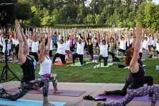 Attendees follow along with a yoga routine during the International Yoga Day celebration, hosted by the Hindu Temple of The Woodlands, on Saturday, June 23, 2018, at Town Green Park.