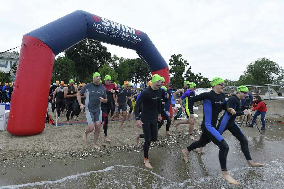 Participants of the 12th annual Swim Across America race into the waters for the Greenwich-Stamford Open Water Swim on June 23, 2018 in Stamford, Connecticut. Participants swam the open waters of the Long Island Sound to the cheers from hundreds of supporters lined up along the shoreline off Cummings Point Road. The event raised more than $343,352 dollars towards supporting the Alliance for Cancer Gene Therapy, the nation's only foundation dedicated exclusively to funding cancer gene therapy research. research. Photo: Matthew Brown / Hearst Connecticut Media / Stamford Advocate