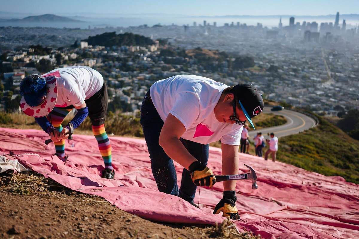 Jessie Wu, right, and Carol Bettencourt, left, nail in the pink tarp during the installation of the Pink Triangle at Twin Peaks in San Francisco, Calif., on Saturday, June 23, 2018.