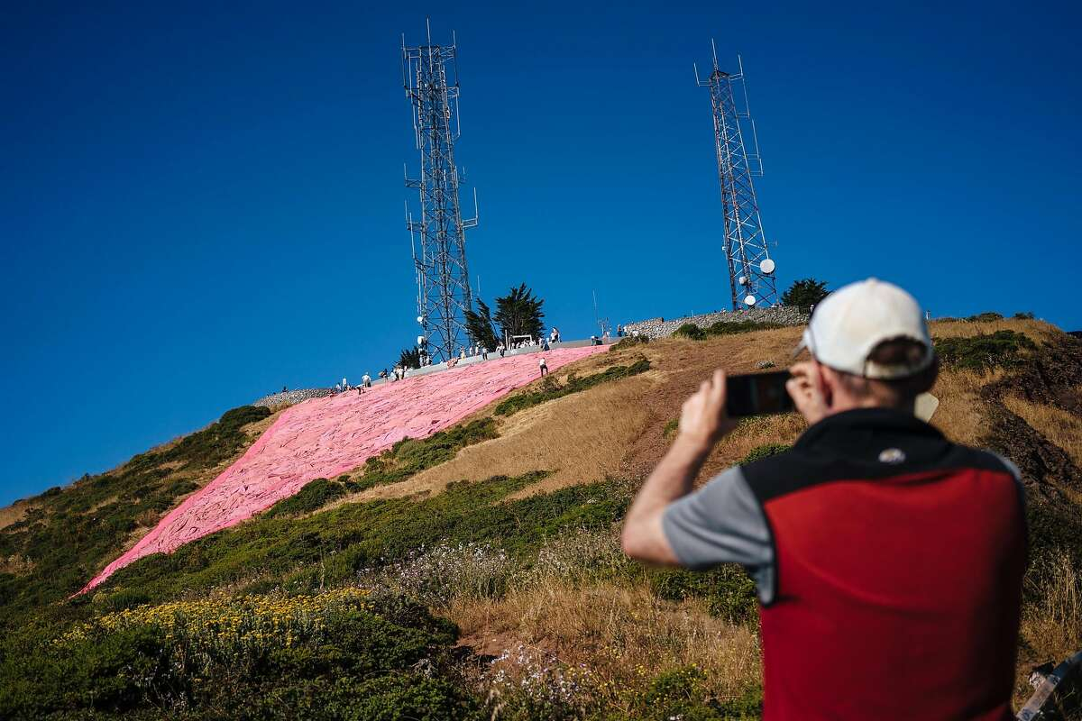 Tom Phelan stops on his run to take a picture of the Pink Triangle at Twin Peaks in San Francisco, Calif., on Saturday, June 23, 2018.