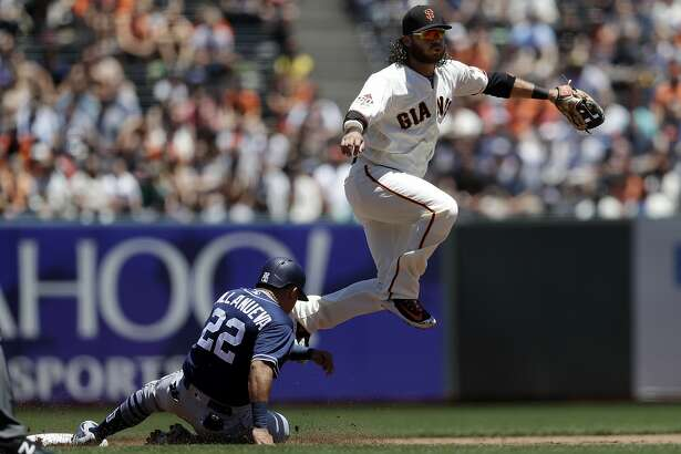 San Francisco Giants shortstop Brandon Crawford, top, completes a double play over San Diego Padres' Christian Villanueva (22) on a ground ball by Jose Pirela during the second inning of a baseball game Saturday, June 23, 2018, in San Francisco. (AP Photo/Marcio Jose Sanchez)