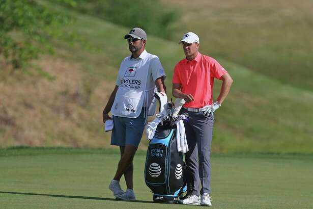 Jordan Spieth talks with his caddie, Michael Greller, on the 13th hole during the second round of the Travelers Championship on Saturday.