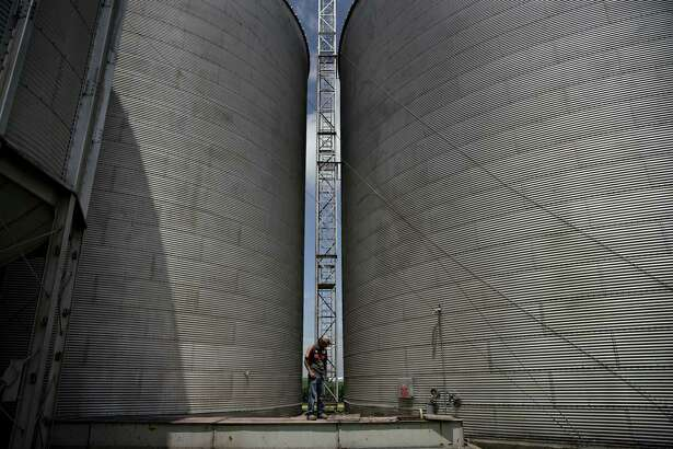 A man monitors a conveyor system at a grain elevator in Ohio, Illinois. Farmers and workers would be hit hard if China imposes agricultural tariffs, targeting many counties that make up the president's base.