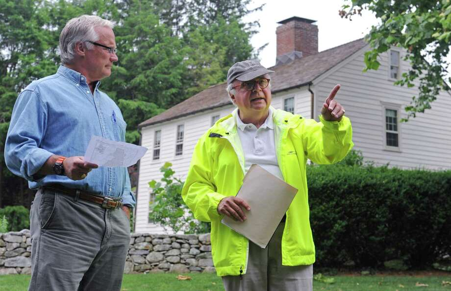 "Westport Historical Society Past President Ed Gerber, right, talks about the history surrounding the a small triangular green at the intersection of Old Hill Road and Kings Highway North that was used as a pre-revolutionary military drill ground as Wesport resident John Threshie looks on during the Westport Historical Society tour of one of the town's oldest settled areas Saturday, June 23,2018, in Westport, Conn. Originally, Kings Highway North was part of a postal road laid out between New York and Boston in 1762. Kings Highway North was established as a local historic district in 1972 and named to the National Register of Historic Places in 1998. It encompasses 106 ""contributing buildings"" – structures that add to the district's historical qualities – and four historic sites. Photo: Erik Trautmann / Hearst Connecticut Media / Norwalk Hour"