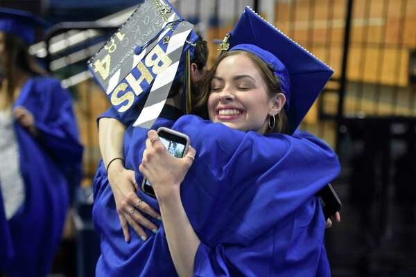 Chloe Sunshine Vettorino gets a hug from class mate Tyler James Pinto before the start of the Brookfield High School 2018 Graduation, Saturday, June 23, 2018, at The O'Neill Center, Western Connecticut State University, Danbury, Conn.
