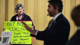 Maggie Clopton Wright holds a sign with her opinio about moving the Cenotaph as Councilman Rpberto Trvino speaks during a community meeting about the proposed changes to Alamo Plaza Thursday evening at the San Antonio Garden Center.