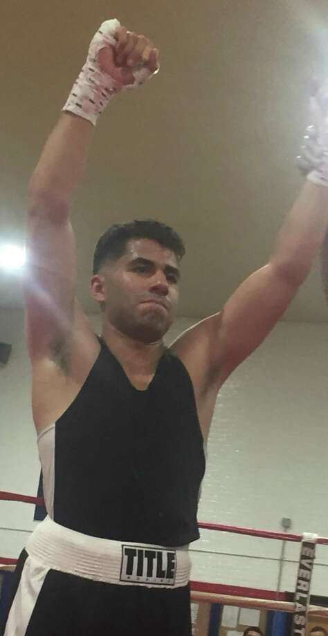 Cesar Collado of Danbury, representing Champs Boxing Club, is declared the winner by technical knockout in his bout at the Summer Sizzler II amateur boxing event at the Danbury War Memorial on Saturday. Photo: Richard Gregory / Hearst Connecticut Media