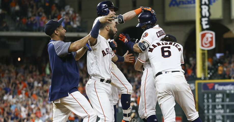 HOUSTON, TX - JUNE 23:  Carlos Correa #1 of the Houston Astros is hugged by Jake Marisnick #6, Josh Reddick #22,Marwin Gonzalez and Yuli Gurriel #10 after hitting a walkoff single in the twelfth inning for a 4-3 win against the Kansas City Royals at Minute Maid Park on June 23, 2018 in Houston, Texas.  (Photo by Bob Levey/Getty Images) Photo: Bob Levey/Getty Images