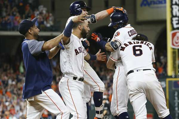 HOUSTON, TX - JUNE 23:  Carlos Correa #1 of the Houston Astros is hugged by Jake Marisnick #6, Josh Reddick #22,Marwin Gonzalez and Yuli Gurriel #10 after hitting a walkoff single in the twelfth inning for a 4-3 win against the Kansas City Royals at Minute Maid Park on June 23, 2018 in Houston, Texas.  (Photo by Bob Levey/Getty Images)