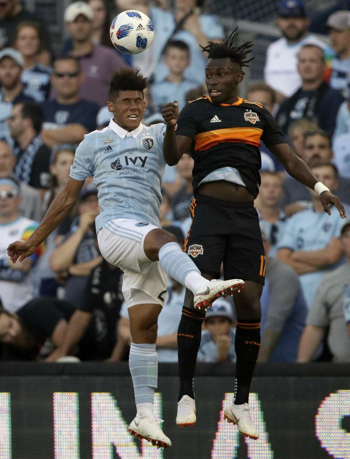 Sporting Kansas City defender Jaylin Lindsey, left, heads the ball against Houston Dynamo forward Alberth Elis, right, during the first half of an MLS soccer match in Kansas City, Kan., Saturday, June 23, 2018. (AP Photo/Orlin Wagner)