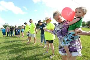 Jessica Ballard holds her son Jackson Lovett as they join hands in a circle of prayer at the start of the Port Acres Neighborhood Appreciation Day in Eagles Park. Port Acres Positive Attitude hosted the free event for neighbors and friends to socialize and show their appreciation for the aid the community received and gave to one another during Harvey. Saturday, June 23, 2018 Kim Brent/The Enterprise