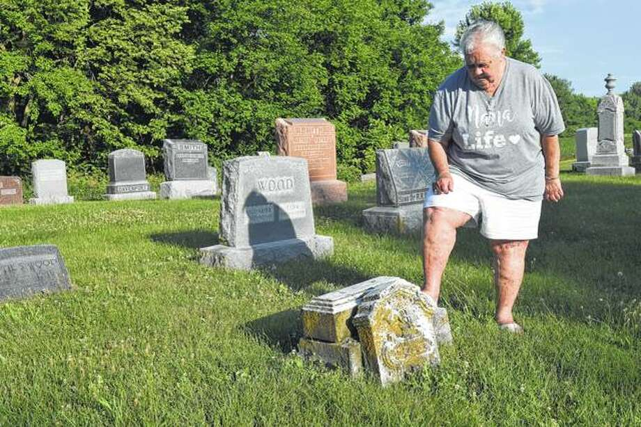Sandy Winner of Jacksonville looks at one of the gravestones that needs to be repaired in Union Baptist Cemetery near Pisgah. Winner and two others are trying to raise money to restore some of the broken tombstones in the old cemetery. Photo:       Greg Olson | Journal-Courier