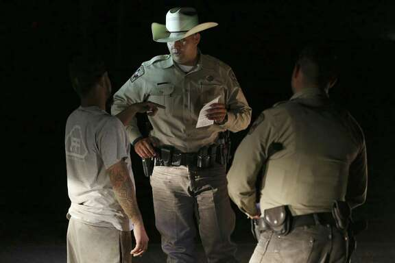 Dimmit County Sheriff's Deputies Jose Diaz, center, and Mike Martinez, right, question a driver near U.S. Highway 83, Thursday, June 21, 2018. They work a highway interdiction detail aimed at human and drug smuggling. The county lies between the Rio Grande border with Mexico and IH-35 making it a hot spot for smugglers. The driver, an oilfield worker, was questioned incorrect temporary license plates and not cited after producing an earlier citation from a Texas Department of Public Safety trooper for the same infraction.