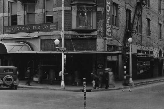 Early in the last century, San Antonio streets were lit by fixtures topped with clear or white glass globes, as shown in this 1920s photo of the Reuter Building at the corner of Crockett and Alamo Plaza; courtesy of Ron Bird, An old metal light fixture owned by a reader is similar to the external lighting used on several local buildings completed in the 1920s; courtesy ITC, A light fixture mounted on the outside of the old Municipal Auditorium (now the Tobin Center for the Performing Arts), as shown in this 1939 photo, has ornate detail similar to one owned by a reader who's trying to identify its original use.