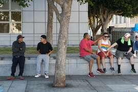 From left, Geraldo Orona and JJ Ramirez watch as friends Jesse Rocha, Joseph Sesate, and German Beltran hang out before the start of the Pride Parade on Sunday, June 24, 2018 in San Francisco, Calif.
