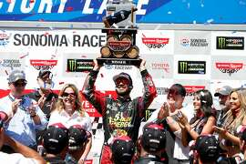 SONOMA, CA - JUNE 24:  Martin Truex Jr., driver of the #78 5-hour ENERGY/Bass Pro Shops Toyota, celebrates in victory lane after winning the Monster Energy NASCAR Cup Series Toyota/Save Mart 350 at Sonoma Raceway on June 24, 2018 in Sonoma, California.  (Photo by Brian Lawdermilk/Getty Images)