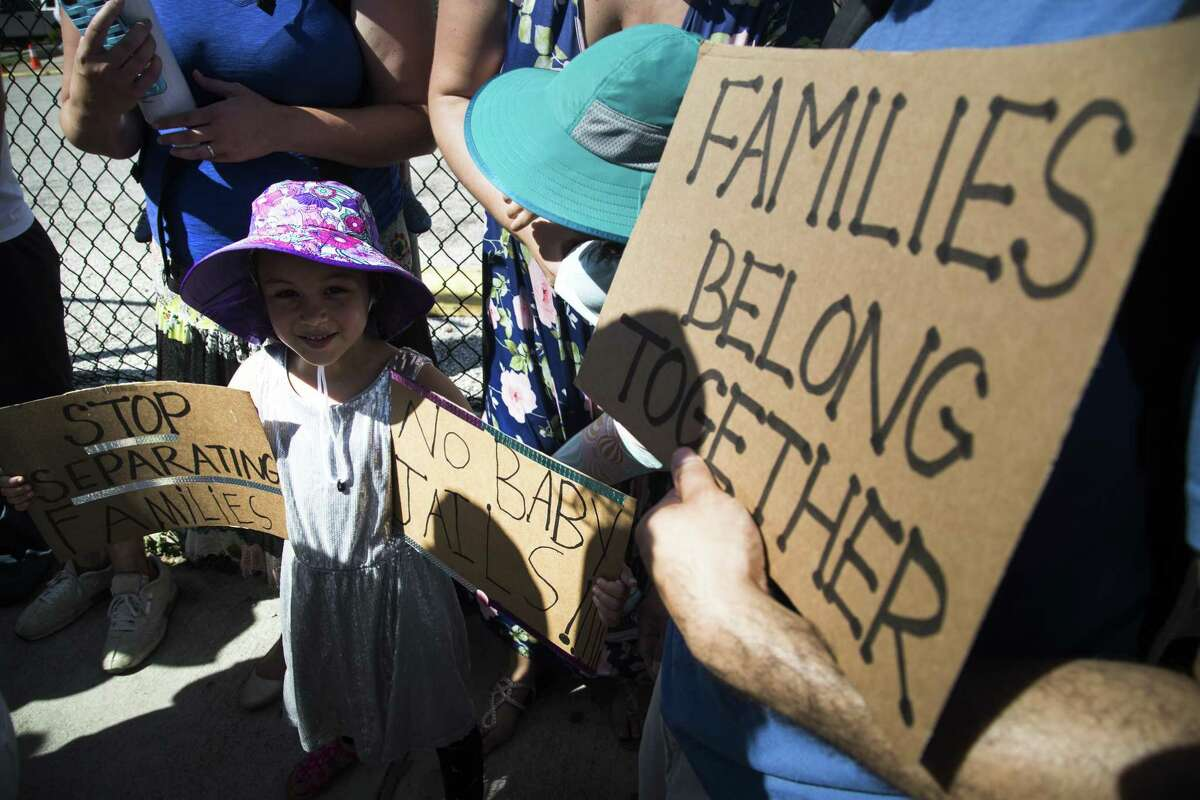 """Maggie Ruiz, 6, holds signs on Sunday, June 24, 2018, protesting """"baby jails"""" in front of a Houston building that has been considered for a shelter for detain immigrant children."""