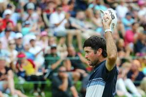 Bubba Watson waves to the gallery after making a putt for birdie on the 18th hole during the final round of the Travelers Championship on Sunday.
