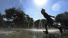 A young boy runs through a fountain of water at Yanaguana Garden and Playground near the Tower of Americas on Tuesday, May 29, 2018.   Hot weather across Texas, with temperatures in the high-90s and 100s, is pushing electricity use to near-record levels.