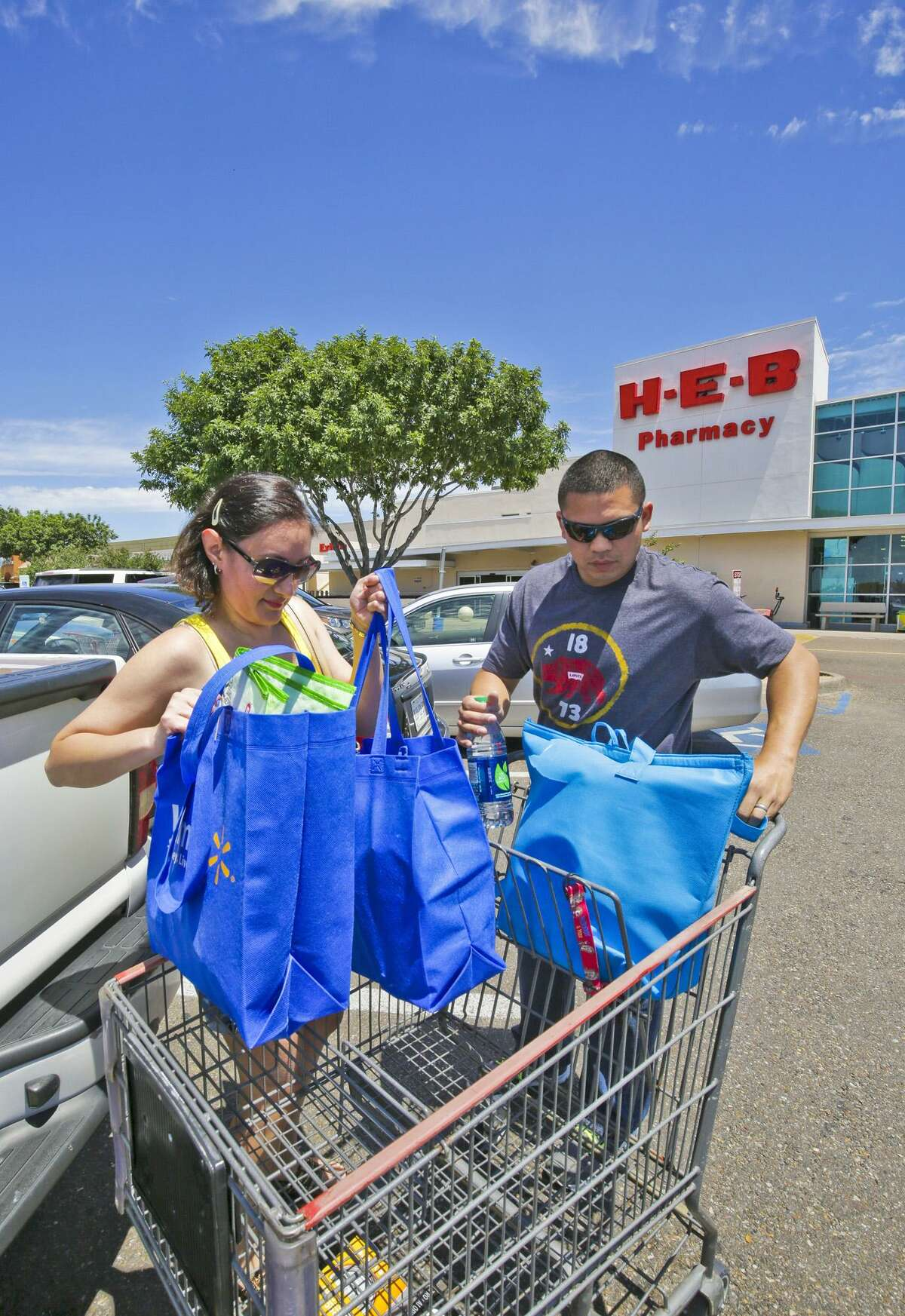 Gladys Delgado and Jose Delgado load reusable grocery bags into their truck after shopping at the H-E-B store on McPherson Rd and Del Mar Blvd in this file photo.