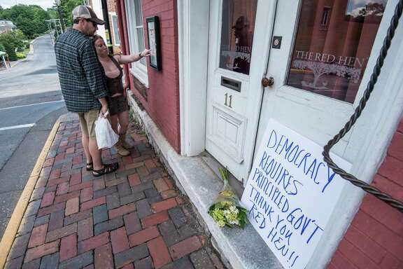 "Passersby examine the menu at the Red Hen Restaurant Saturday, June 23, 2018, in Lexington, Va. White House press secretary Sarah Huckabee Sanders said Saturday in a tweet that she was booted from the Virginia restaurant because she works for President Donald Trump. Sanders said she was told by the owner of The Red Hen that she had to ""leave because I work for @POTUS and I politely left."" /Daily News-Record via AP)"