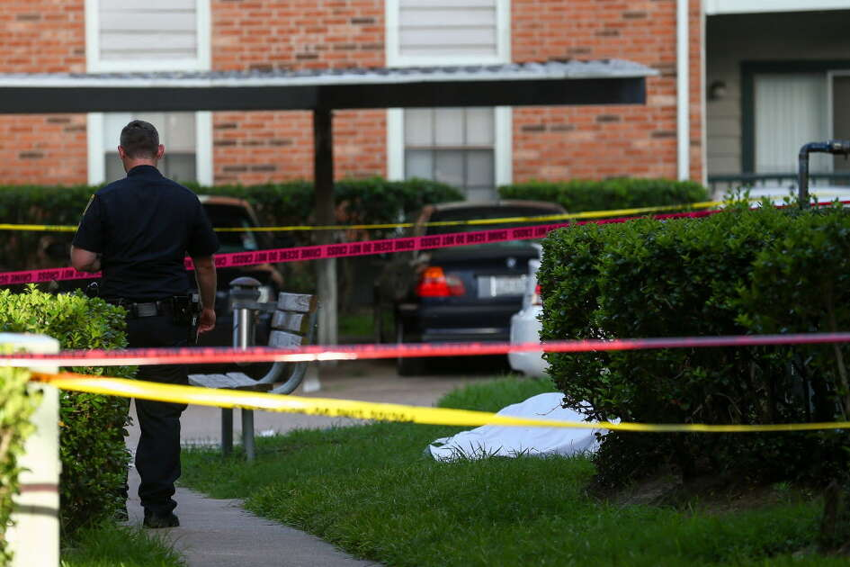 Houston Police officers investigate the scene where two people were found dead at an apartment complex on he 1300 block of Gears Road Monday, June 25, 2018, in Houston.