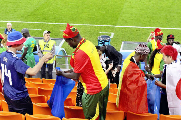 Japanese and Senegalese supporters collect garbage after the game in Yekaterinburg, Russia, on Sunday.