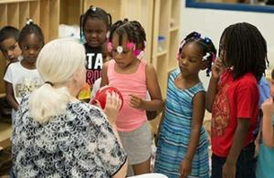 "Martha Latorre, PhD, associate professor in SIUE's Department of Teaching and Learning and director of the Early Childhood Education program, gives instruction on making a ""bird's egg."" Photo:       For The Telegraph"
