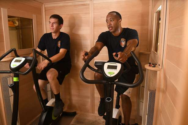 Cadet firefighters Colton Allen, 20, left, and Bradley Whitlock, 32, of Spring Fire Dept. Station 70, ride exercise bikes in the medical grade dry (detoxification) sauna that crew members use after responding to a fire call at the station on June 19, 2018. (Jerry Baker/For the Chronicle)